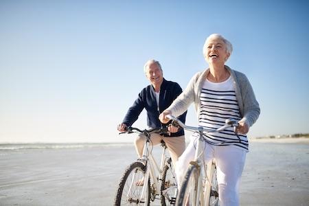 älteres Seniorenpaar auf zwei Fahrrädern lachend am Strand.png