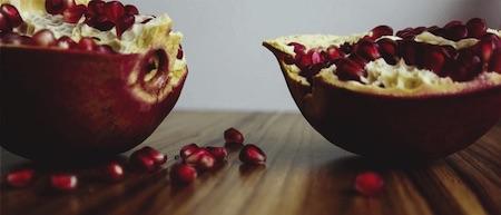Jarrow PomeGuard halbierter Granatapfel auf Holz mit losen Granatapfelkernen.png