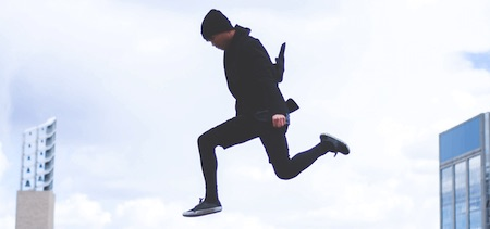 Jarrow Q-absorb springender Mann in schwarzen Klamotten zwischen 2 Gebäuden.png